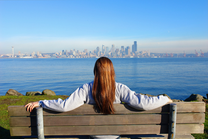 Woman sitting in wooden bench watching the city view