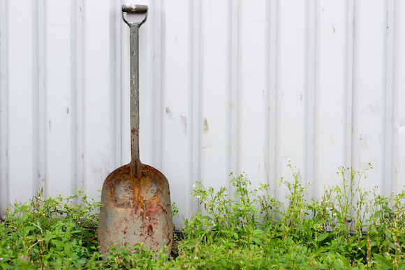 rusty shovel leaning on shed
