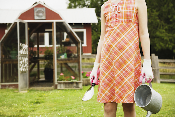 woman holds garden supplies at farm