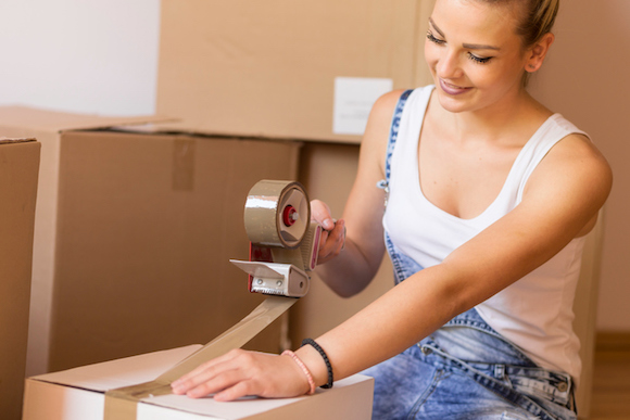 Young girl moving in a new apartment,standing surrounded with cardboard boxes, packing and taping boxes