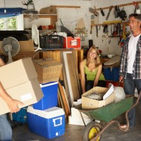 Teenage Family Clearing Garage For Yard Sale Laughing Together