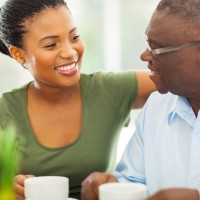 smiling elderly african american man enjoying coffee with his granddaughteer at home