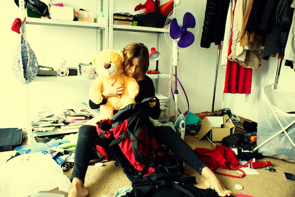 woman is packing backpack in a messy room