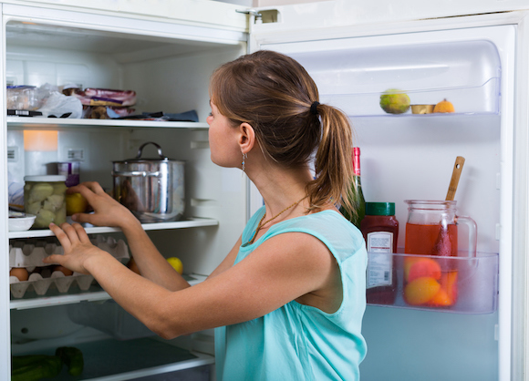 Young woman standing near refrigerator filled with products