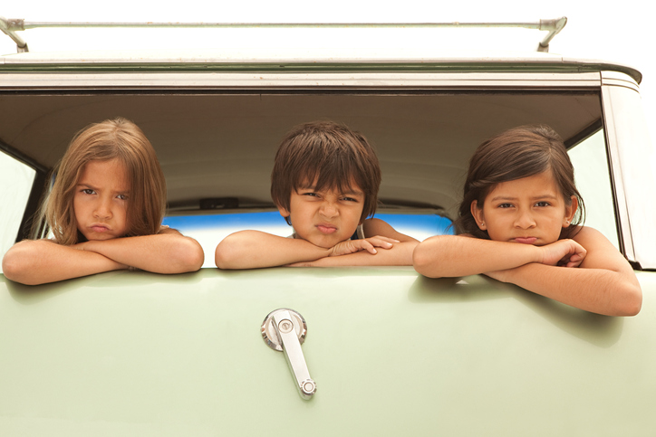 Three sullen children in back of estate car