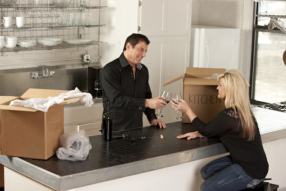Couple Makes a Toast With Wine and Unpacks Boxes
