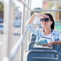 young woman touring the city on open top bus