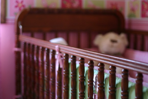 A baby crib with a narrow depth of field, focused towards right of image.