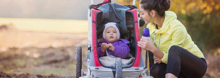 Beautiful young mother with her daughter in jogging stroller running outside in autumn nature