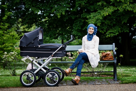 Woman in headscarf with stroller in park