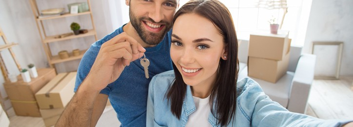 Young couple man and woman moving to a new apartment together relocation using digital device