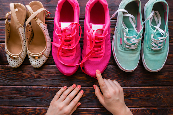 girl chooses shoes on a wooden background